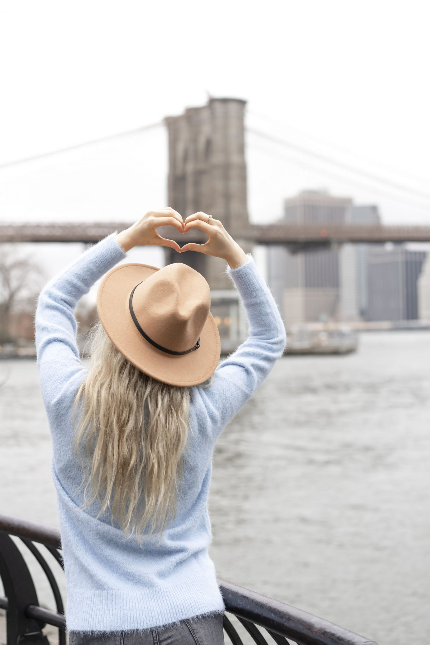 girl with heart hands pointing to the Brooklyn Bridge