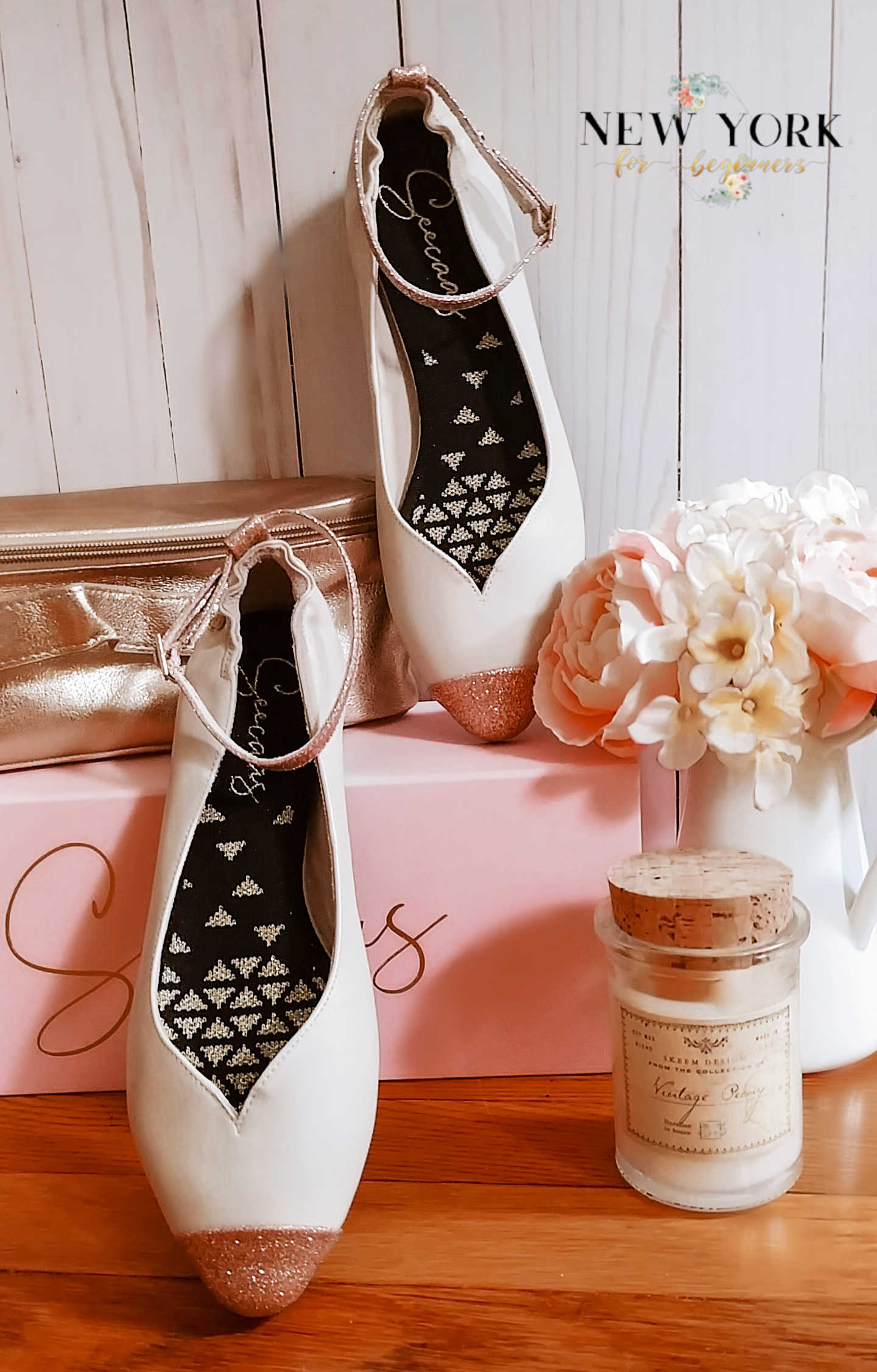 A Seecas pair of pink flats with a white vase with pink and white roses